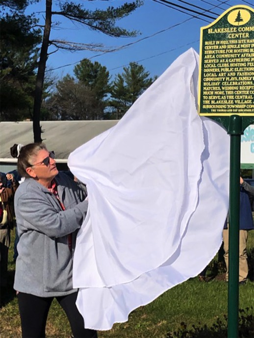 Blakeslee Community Association board member Lorraine Koscuiskl unveils the marker.