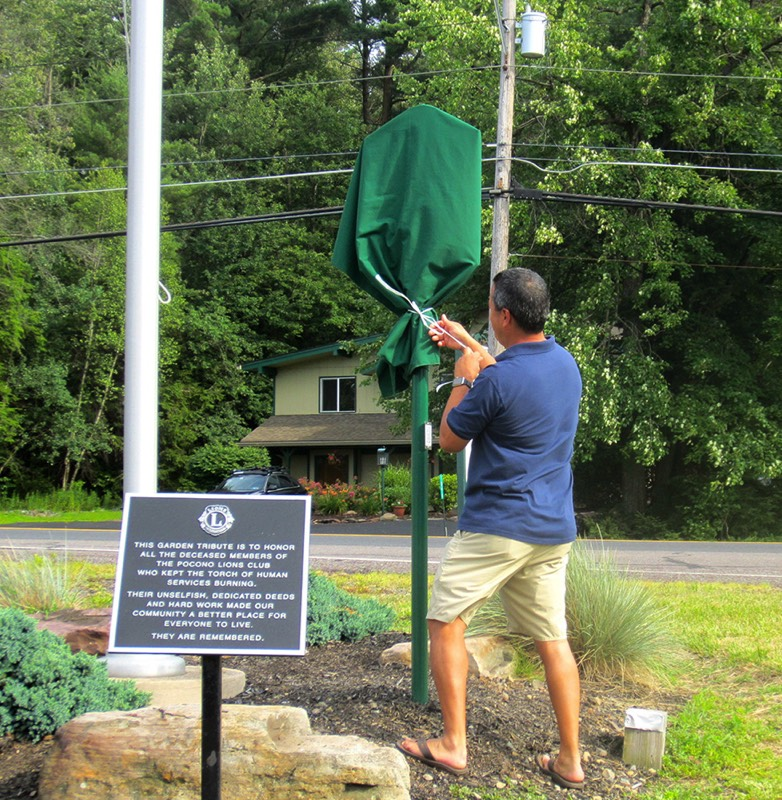 Sean Naughton, president of the Pocono Lions Club, starts to unveil the Tobyhanna Township historical marker.
